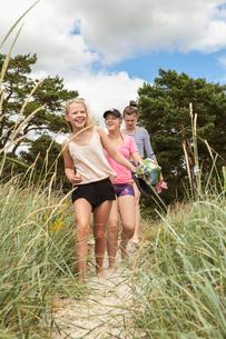 Sweden, Blekinge, Solvesbor, Torso, Teenage girls (14-15) walking in line through grassの写真素材 [FYI02704505]