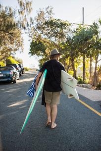 Australia, Queensland, Sunshine Coast, Noosa, Alexandria Bay, Young man carrying surfboardの写真素材 [FYI02704510]