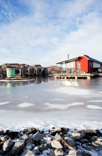 Sweden, Bohuslan, Orust, Skarhamn, Wooden house by frozen seaの写真素材 [FYI02704516]