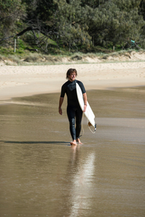 Australia, Queensland, Sunshine Coast, Noosa, Alexandria Bay, Young man carrying surfboard on beachの写真素材 [FYI02704517]