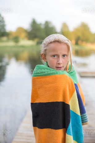 Sweden, Smaland, Braarpasjon, Portrait of girl (10-11) wrapped in towel after swimming in lakeの写真素材 [FYI02704529]