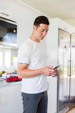 Sweden, Man using mobile phone in kitchenの写真素材 [FYI02704533]