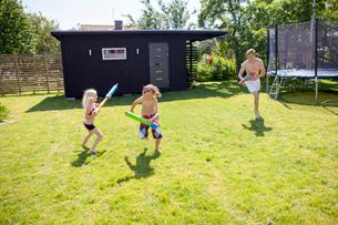Sweden, Vastergotland, Lerum, Siblings (8-9, 10-11) playing with water guns in backyardの写真素材 [FYI02704537]