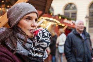 Sweden, Stockholm, Gamla Stan, Woman drinking coffee at marketの写真素材 [FYI02704540]