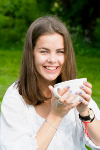 Sweden, Sodermanland, Stockholm, Portrait of young woman drinking from cup in parkの写真素材 [FYI02704547]