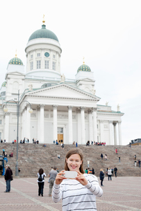 Finland, Uusimaa, Helsinki, Senaatintori, Young woman photographing self with Lutheran Cathedral inの写真素材 [FYI02704559]
