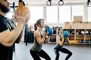 Germany, Young women and man cross training with kettlebells in gymの写真素材 [FYI02704580]