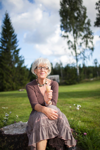 Sweden, Medelpad, Portrait of senior woman sitting on tree stump and eating ice-creamの写真素材 [FYI02704615]