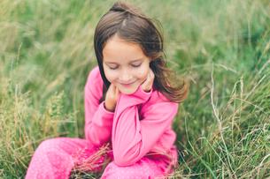 Sweden, Blekinge, Girl (8-9) in pink clothes sitting in grassの写真素材 [FYI02704620]