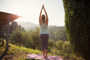 Italy, Tuscany, Dicomano, Woman practicing yoga against green hillsの写真素材 [FYI02704624]