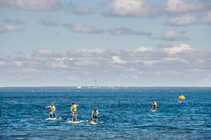 Finland, Varsinais-Suomi, Eura, Lake Pyhajarvi, Young men paddleboarding on lakeの写真素材 [FYI02704625]
