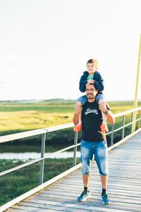 Germany, Schleswig-Holstein, Kreis Nordfriesland, Portrait of father giving son (8-9) piggyback rideの写真素材 [FYI02704631]