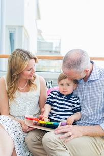 Sweden, Sodermanland, Nacka, Finnboda Hamn, Grandfather and grandmother sitting with baby boy on balの写真素材 [FYI02704660]