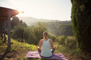 Italy, Tuscany, Dicomano, Woman in lotus position facing green hillsの写真素材 [FYI02704668]
