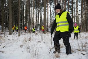 Sweden, Uppland, Upplands Vasby, Volunteers of Missing people organization in winter forestの写真素材 [FYI02704678]