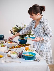 Sweden, Woman serving foodの写真素材 [FYI02704680]