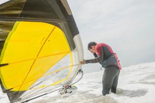 Portugal, Lisbon, Praia do Guincho, Man preparing windsurfing board in wavesの写真素材 [FYI02704691]