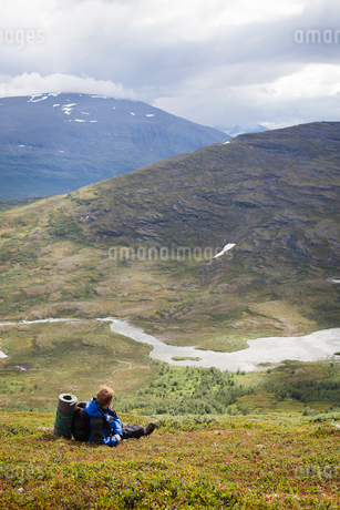 Sweden, Lapland, Abisko, Backpacker sitting on mountain slope and looking at viewの写真素材 [FYI02704706]