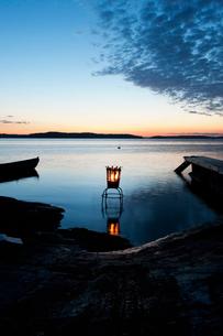 Sweden, Stockholm, Sodermanland, Dalaro, Lantern on lake at sunsetの写真素材 [FYI02704708]