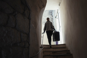 France, Languedoc-Roussillon, Sauve, Young woman carrying luggage on staircaseの写真素材 [FYI02704713]
