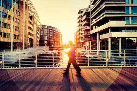 Norway, Oslo, Aker Brygge, Pedestrians on city bridge silhouetted against setting sunの写真素材 [FYI02704721]