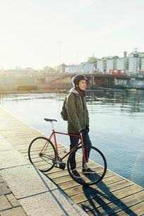 Sweden, Sodermanland, Stockholm, Sodermalm, Slussen, Mid adult man standing with fixed gear bike onの写真素材 [FYI02704726]