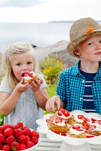 Sweden, Uppland, Roslagen, Children (6-7, 8-9) eating strawberry dessert outdoorsの写真素材 [FYI02704730]