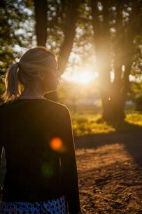 Sweden, Uppland, Orbyhus, Woman on dirt road at sunsetの写真素材 [FYI02704733]