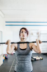 Germany, Young woman training with barbell in gymの写真素材 [FYI02704740]