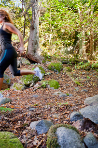 Sweden, Sodermanland, Stockholm County, Nacka, Mid adult woman running through forestの写真素材 [FYI02704745]