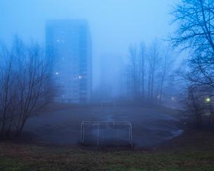 Sweden, Skane, Malmo, Hogaholm, Almvik, Residential buildings with soccer field in foreground in fogの写真素材 [FYI02704747]