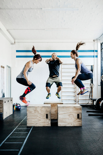 Germany, Young women and man jumping in gymの写真素材 [FYI02704754]