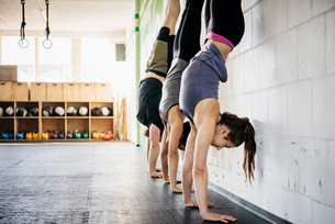 Germany, Young women and man practicing handstand in gymの写真素材 [FYI02704756]