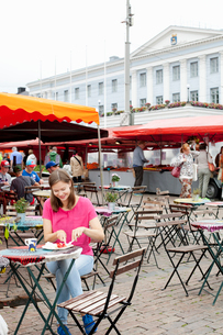 Finland, Uusimaa, Helsinki, Kauppatori, Young woman eating street food in open air restaurantの写真素材 [FYI02704758]