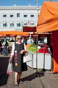 Finland, Helsinki, Kauppatori, Smiling senior woman at street marketの写真素材 [FYI02704761]