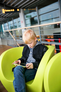 Germany, Hamburg, Boy (8-9) sitting at airport hall and using tabletの写真素材 [FYI02704764]