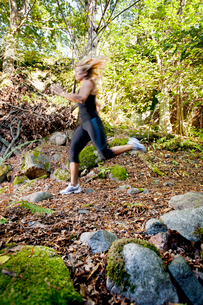 Sweden, Sodermanland, Stockholm County, Nacka, Mid adult woman running through forestの写真素材 [FYI02704791]