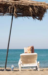 Greece, Karpathos, Woman sunbathing and reading book at beachの写真素材 [FYI02704803]