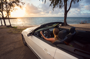 USA, Hawaii, Oahu, Banzai Pipeline, Mid adult woman watching sunset in convertible car at beachの写真素材 [FYI02704829]