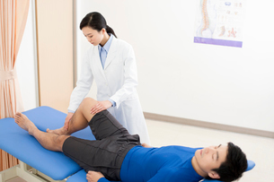 Female doctor examining patientの写真素材 [FYI02704855]