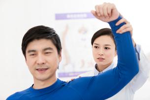 Female doctor examining patientの写真素材 [FYI02704857]
