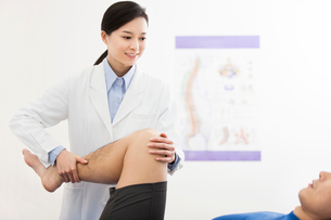 Female doctor examining patientの写真素材 [FYI02704865]