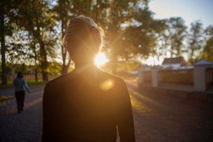 Sweden, Uppland, Orbyhus, Woman in street at sunsetの写真素材 [FYI02704888]