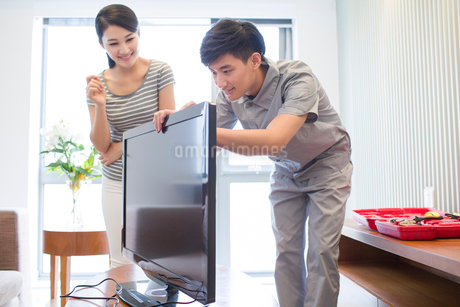 Engineer repairing television in customer's homeの写真素材 [FYI02704969]