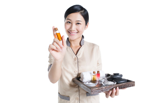 Massage therapist showing massage suppliesの写真素材 [FYI02704980]