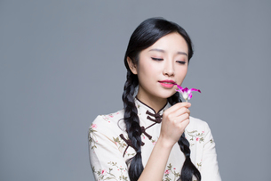 Young beautiful woman in traditional cheongsam with orchidの写真素材 [FYI02705067]