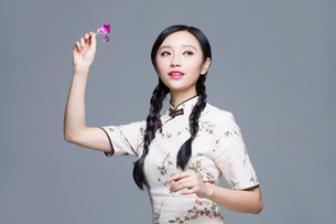 Young beautiful woman in traditional cheongsam with orchidの写真素材 [FYI02705072]