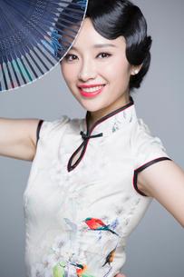 Young beautiful woman in traditional cheongsam with folding fanの写真素材 [FYI02705099]