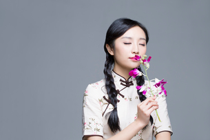 Young beautiful woman in traditional cheongsam with orchidの写真素材 [FYI02705118]