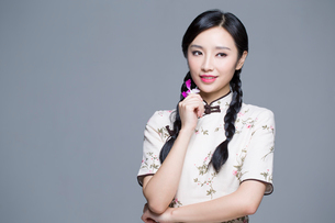 Young beautiful woman in traditional cheongsam with orchidの写真素材 [FYI02705135]